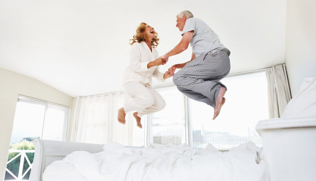 Excited senior couple jumping on their bed at home