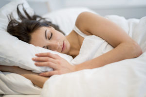 Woman sleeping at home in her bed
